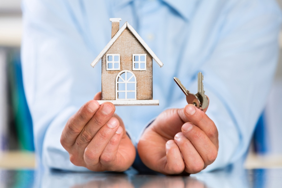 Male Hands holding Miniature House and House Key. Real Estate Property Concept.