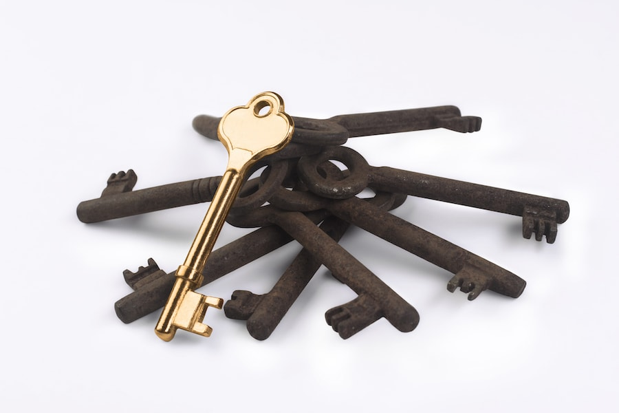 A golden key sitting on a bunch of rusty keys isolated on white background.