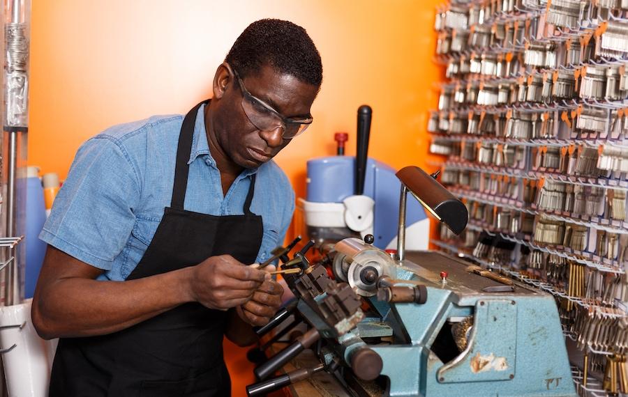 Focused experienced locksmith working on key duplicating machine in workshop in Saint Clair Shores, MI.