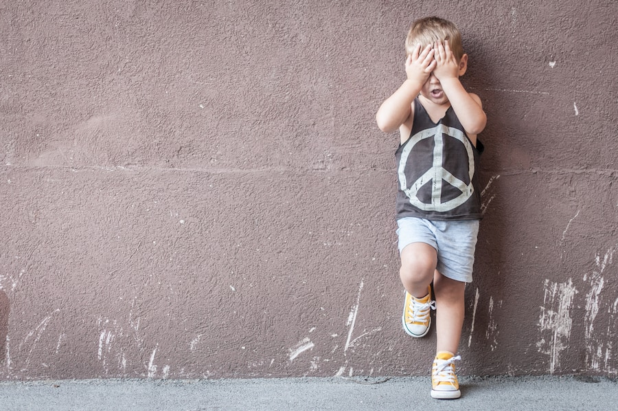 Sad boy over textured wall background with space for text.