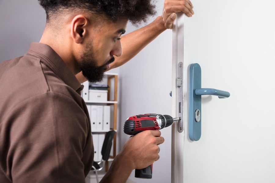 Close-up Of A Young Male Carpenter Installing Door Lock With Wireless Screwdriver.