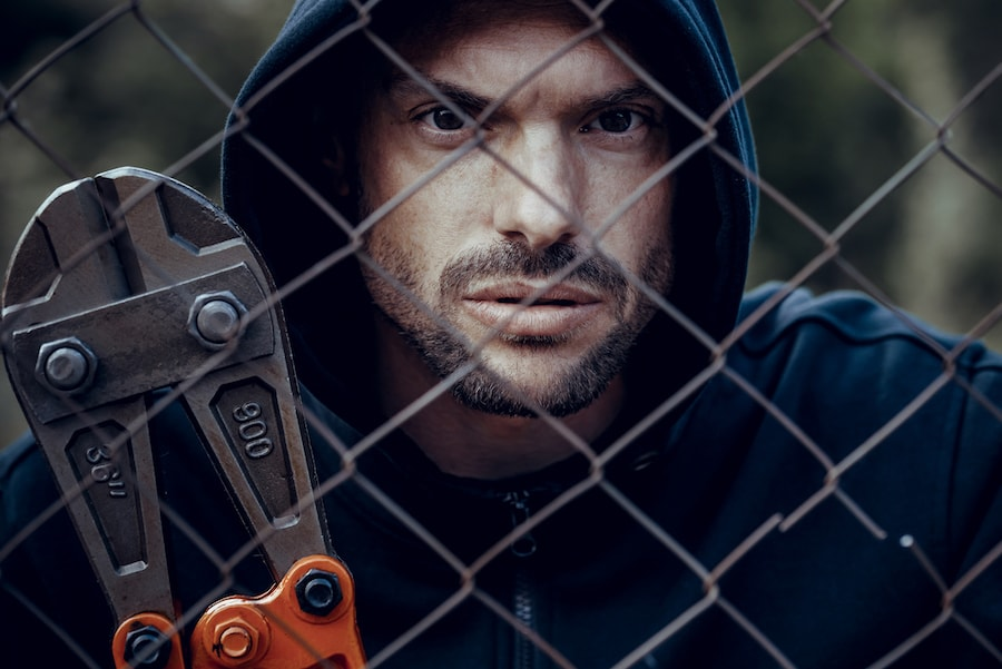 Thief with bolt cutter behind the fence.