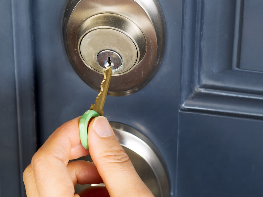 Female hand putting house key into door lock