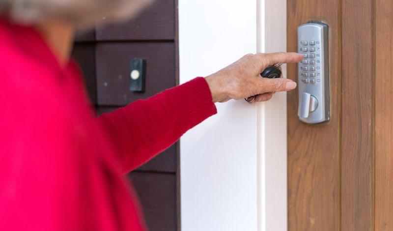 Senior woman uses keypad on digital lock to unlock and open domestic front door